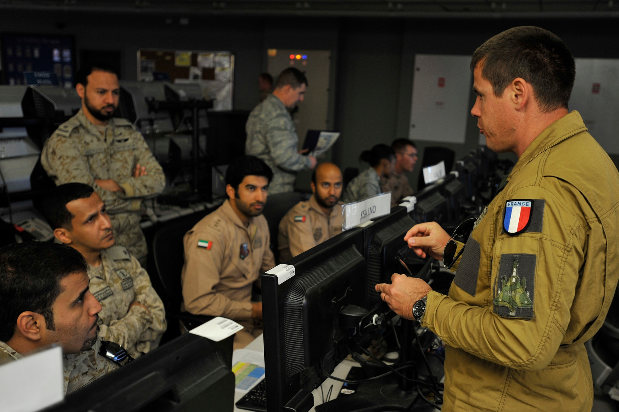 Armee De l'Air Lt. Col. Eric Konietzko, Course Director, briefs the Liaison Officer (LNO) students during Arabian Gulf Shield, Feb. 3, 2016, in the Combined Air Operations Center, Al Udeid Air Base, Qatar. Arabian Gulf Shield is the culminating exercise for the Gulf Cooperation Council (GCC) LNO Program. The exercise is designed to exercise GCC LNO procedures and connectivity to host nation Air Operations Centers which improves US-GCC interoperability. (U.S. Air Force photo by Master Sgt. Joshua Strang)