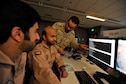 Royal Saudi Air Defense Forces Capt. Mofareh Al-Faifi (far right) coordinates with United Arab Emirates Air Force Maj. Salem Al Kaabi and Capt. Salem Alderei during Arabian Gulf Shield, Feb. 3, 2016, in the Combined Air Operations Center, Al Udeid Air Base, Qatar. Arabian Gulf Shield is the culminating exercise for the Gulf Cooperation Council (GCC) Liaison Officer (LNO) Program. The exercise is designed to exercise GCC LNO procedures and connectivity to host nation Air Operations Centers which improves US-GCC interoperability. (U.S. Air Force photo by Master Sgt. Joshua Strang)