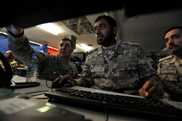 1st Lt. Joshua Skoglund, exercise coordinator, assists Qatar Emiri Air Force Capt. Ghanim Al-Mohannadi and Maj. Rashid Al-Haytamy during Arabian Gulf Shield, Feb. 3, 2016, in the Combined Air Operations Center, Al Udeid Air Base, Qatar. Arabian Gulf Shield is the culminating exercise for the Gulf Cooperation Council (GCC) Liaison Officer (LNO) Program. The exercise is designed to exercise GCC LNO procedures and connectivity to host nation Air Operations Centers which improves US-GCC interoperability. (U.S. Air Force photo by Master Sgt. Joshua Strang)