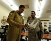 Armee De l'Air Lt. Col. Eric Konietzko (left), Course Director, looks at a momento from his students while talking to  Royal Saudi Air Defense Forces Maj. Mansour Almutrif after a graduation ceremony, Feb. 4, 2016, in the Combined Air Operations Center, Al Udeid Air Base, Qatar. The ceremony recognized the achievement of the students completion of the Gulf Cooperation Council (GCC) Liaison officer Program and the Senior Operations Planner Program of which Almutrif was a senior planner. Both programs improve interoperability and furthers relations within the GCC and the U.S. air and air defense community. (U.S. Air Force photo by Master Sgt. Joshua Strang)