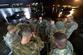 Soldiers and airmen receive a mission brief before working together to load an AH-64 Apache helicopter onboard a C-17 Globemaster III in support of large package week operations on Pope Army Airfield, N.C., Feb. 4, 2016. The soldiers are assigned to the 82nd Airborne Division's 82nd Combat Aviation Brigade and the airmen are assigned to the 517th Airlift Squadron, 3rd Airlift Wing deployed from Joint Base Elmendorf-Richardson, Alaska. The training prepares Army and Air Force units for worldwide crisis and contingency operations. Air Force photo by Staff Sgt. Paul Labbe