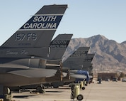 F-16 Fighting Falcons aircraft await the first sortie of the day during exercise Red Flag 16-1 on Nellis Air Force Base, Nev., Jan. 26, 2016. The aircraft are assigned to the South Carolina Air National Guard's 157th Fighter Squadron, McEntire Joint National Guard Base, S.C. The exercise provides realistic combat training to maximize the combat readiness and survivability of participants by providing a realistic training environment. Air Force photo by Master Sgt. Burt Traynor
