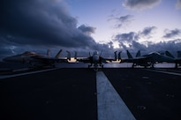 The sun rises behind F/A-18 Super Hornets on the flight deck of the USS John C. Stennis in the Pacific Ocean, Jan. 28, 2016. Navy photo by Seaman Cole C. Pielop