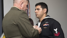 Major Gen. Joseph L. Osterman, commander, U.S. Marine Corps Forces, Special Operations Command, presents Petty Officer 2nd Class Alejandro Salabarria, a corpsman with Marine Special Operations Company F, 2nd Marine Raider Battalion, the Silver Star Medal during a ceremony at Stone Bay, Marine Corps Base Camp Lejeune, North Carolina, Feb. 5, 2016. Salabarria was awarded for his actions in Afghanistan Sept. 15, 2014.