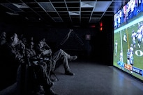 Service members and civilian contractors watch the Denver Broncos and Carolina Panthers compete in Super Bowl 50 during a viewing party at Bagram Airfield, Afghanistan, Feb. 8, 2016. Miami Dolphins cheerleaders and former players joined troops at Bagram for the event. Air Force photo by Tech. Sgt. Nicholas Rau