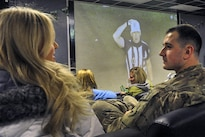A service member talks with a Miami Dolphins cheerleader during a Super Bowl 50 viewing party at Bagram Airfield, Afghanistan, Feb. 8, 2016. Air Force photo by Tech. Sgt. Nicholas Rau