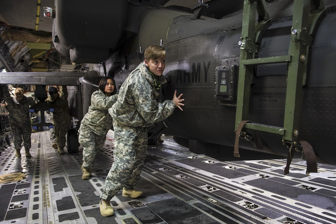Soldiers and airmen work together to upload an AH-64 Apache helicopter onboard a C-17 Globemaster III to support training operations on Pope Army Airfield, N.C., Feb. 4, 2016. Air Force photo by Staff Sgt. Paul Labbe