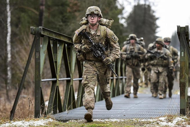 Army Spc. Shane Rader runs during a 12-mile ruck march as part of the testing phase for the expert infantryman badge at the 7th Army Joint Multinational Training Command's Grafenwoehr Training Area, Germany, Feb. 5, 2016. Bader is a paratrooper assigned to the 173rd Airborne Brigade. Army photo by Gertrud Zach