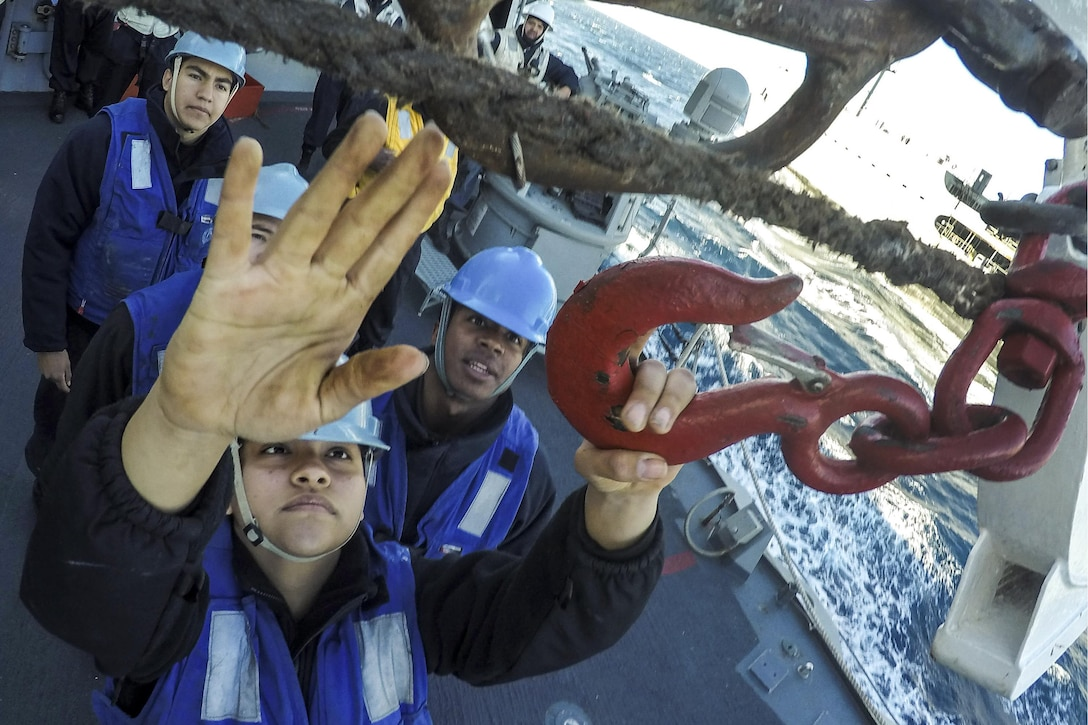 Navy Seaman Lisette Longoria connects the surf hook during a replenishment aboard the USS Carney in the Mediterranean Sea, Feb. 7, 2016. The guided-missile destroyer is supporting U.S. national security interests in Europe. U.S. Navy photo by Petty Officer 1st Class Theron J. Godbold