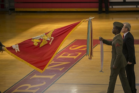 Private First Class Deleano Francis, accompanied by Sergeant Major (Ret.) Bret Roy, of the 2nd Marine Division Association, present attach a streamer to the 2nd Marine Division battle colors during a rededication and award ceremony at Camp Lejeune, N.C., Feb. 5, 2016. The division rededication ceremony is one of the first events in the celebration of the 75th anniversary of 2nd Marine Division. (U.S. Marine Corps photo by Lance Cpl. Luke Hoogendam/Released)