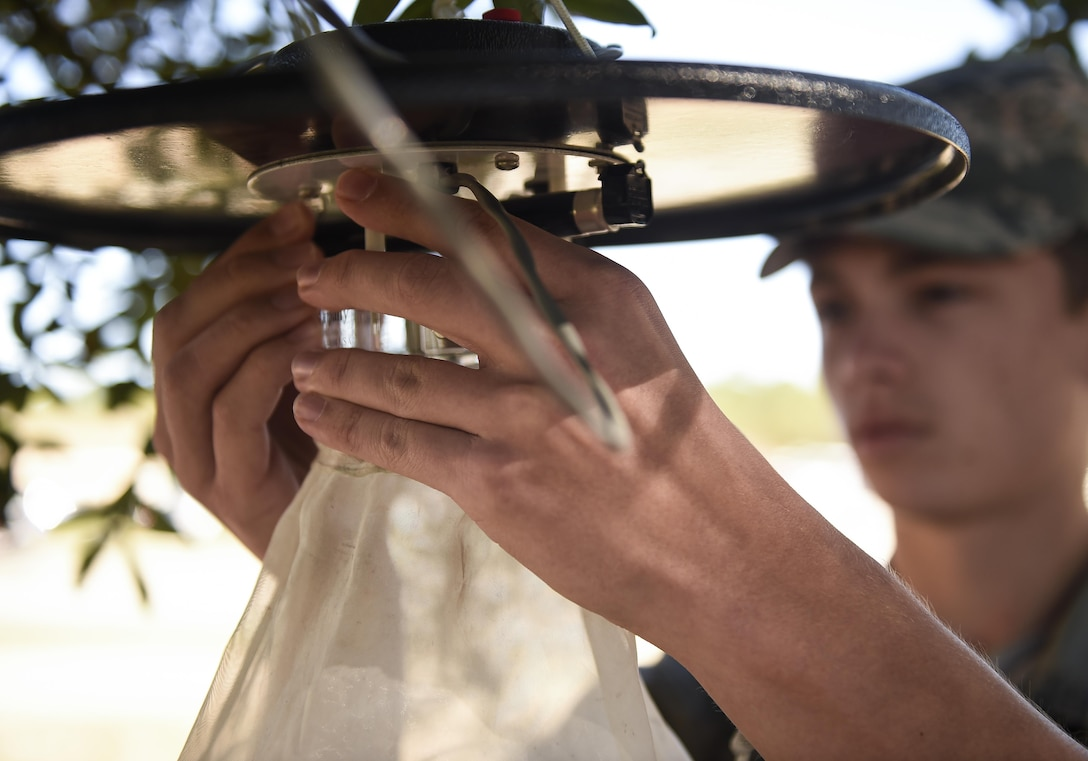 Airman 1st Class Kyle Engle, a public health technician with the 1st Special Operations Medical Group, hangs a mosquito trap in a tree at Hurlburt Field, Fla., Feb. 5, 2016. The mosquito traps will be hung around Hurlburt to catch specimens for later identification in a lab at Wright-Patterson Air Force Base, Ohio. (U.S. Air Force photo by Airman 1st Class Kai White)
