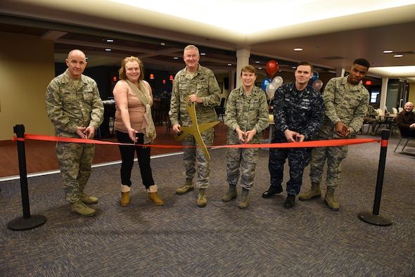 """Members of the 911th Airlift Wing and the Navy Operational Support Center Pittsburgh cut the ceremonial ribbon at the grand opening of the new Cargo Bay Community Center, Pittsburgh International Airport Air Reserve Station, Feb. 6, 2016. The new community center houses increased seating with an open concept floor plan, a separate """"demilitarized"""" gaming zone and a new bar. (U.S. Air Force photo by Staff Sgt. Justyne Obeldobel)"""
