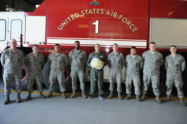 Michael Oliver, Pilot for a Day participant, poses for a group photo with fire fighters from the 11th Civil Engineer Squadron at Joint Base Andrews, Md., Feb. 5, 2016. Oliver, diagnosed with Erdheim-Chester Disease, a disease with no known cure, experienced what it is like to be a pilot for a day along with friends and family. The day included touring an assortment of aircraft including an F-16 Fighting Falcon, KC-135 Stratotanker and a UH-1N Huey helicopter. (U.S. Air Force photo by Senior Airman Dylan Nuckolls/Released)