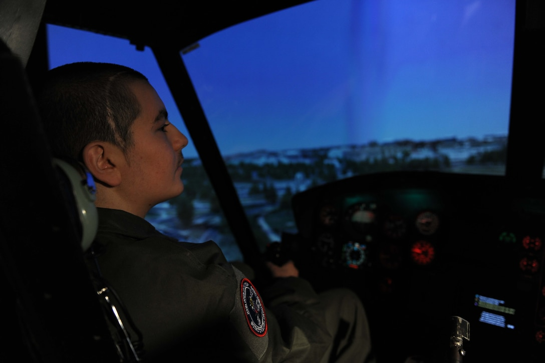 Michael Oliver, Pilot for a Day participant, flies in the UH-1N Huey helicopter simulator at Joint Base Andrews, Md., Feb. 5, 2016. Oliver, diagnosed with Erdheim-Chester Disease, a disease with no known cure, experienced what it is like to be a pilot for a day along with friends and family. The day included touring an assortment of aircraft including an F-16 Fighting Falcon, KC-135 Stratotanker and a UH-1N Huey helicopter. (U.S. Air Force photo by Senior Airman Dylan Nuckolls/Released)