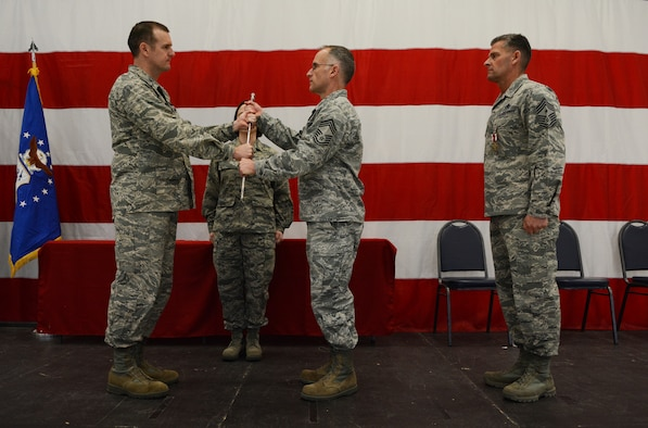 Col. Jeffrey Wiegand, 115th Fighter Wing commander, passes the sword to Chief Master Sgt. James C. McKay, III, 115 FW command chief, during the change of authority ceremony in Hangar 406 Feb. 7, 2016. McKay took over command from Chief Master Sgt. Thomas J. Safer, now the state command chief. (U.S. Air National Guard photo by Senior Airman Kyle Russell)