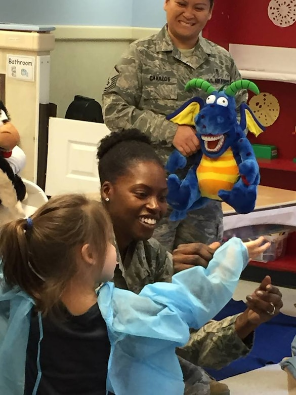 On Feb. 5, members of the Dental Squadron from the 779th Medical Group went to the Child Development Center on Joint Base Andrews to teach the kids about good dental health.  Tech. Sgt. Tina Phelps-Prince, NCOIC for preventive dentistry, helped one member of the class to dress up as a dentist.  (AF photo by Melanie Moore/Released)