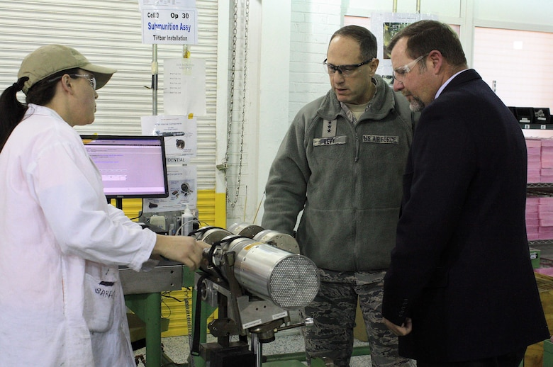 Lauren Miller (left), an explosives production operator, talks to Lt. Gen. Lee K. Levy II, commander, Air Force Sustainment Center at Tinker Air Force Base, Okla., and Chris Scott, McAlester Army Ammunition Plant site leader for Textron Defense Systems, about the CBU-105 Sensor Fuzed Weapon during a visit to the facility in Oklahoma, Jan. 11. (U.S. Army photo by Kevin Jackson)