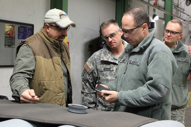 Lt. Gen. Lee K. Levy II, commander, Air Force Sustainment Center at Tinker Air Force Base, Okla., examines a retention ring used on the aft end of a general purpose bomb as Jerry Lovell (far left), Col. Sean M. Herron and Chief Master Sgt. Jason France listen intently.   (U.S. Army photo by Kevin Jackson)