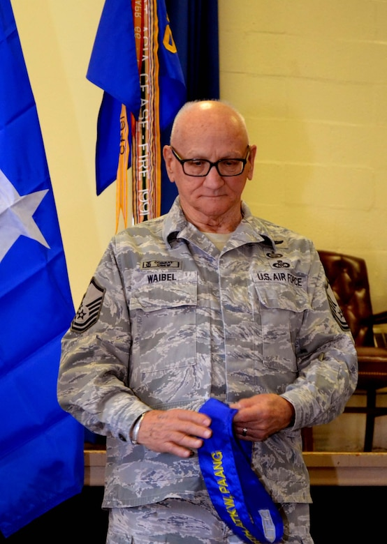 Retired Master Sgt. Jim Waibel, the 111th Attack Wing historian, clutches the 111th Air Operations Group streamer after it had been removed during a deactivation ceremony held Feb. 6, 2016 at Horsham Air Guard Station, Pennsylvania. The 111th AOG was a high-tempo operations group on base for five years. (U.S. Air National Guard photo by Tech. Sgt. Andria Allmond)
