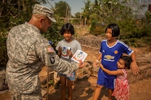 A U.S. Army soldier passes out exercise Cobra Gold 2016 stickers to Thai civilians in Lop Buri, Thailand, exercise Cobra Gold, Jan. 23, 2016. Cobra Gold 2016, in its 35th iteration, includes a specific focus on humanitarian civic action, community engagement and medical activities conducted during the exercise to support the needs and humanitarian interests of civilian populations around the region.
