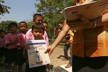 Chomanee Chomnamul, an elementary school teacher at Ban Sa Yai School in Trat, Thailand, passes out coloring books during exercise Cobra Gold, Feb. 3, 2016. Cobra Gold 2016, in its 35th iteration, includes a specific focus on humanitarian civic action, community engagement and medical activities conducted during the exercise to support the needs and humanitarian interests of civilian populations around the region.