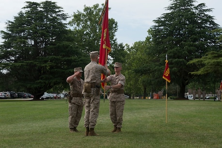 U.S. Marine Col. James M. Bright, the outgoing commanding officer of the Marine Corps Security Force Regiment, passes the regimental colors to incoming regimental commanding officer, U.S. Marine Col. John W. Evans, during the change-of-command ceremony June 19 at Naval Weapons Station Yorktown, Va. The exchanging of regimental colors represents the passing of command from the outgoing to the incoming commanding officer.
