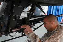A soldier removes a portion of a weapon system while preparing an AH-64 Apache helicopter for transport at Fort Bragg, N.C., Feb. 2, 2016. Army photo by Staff Sgt. Christopher Freeman