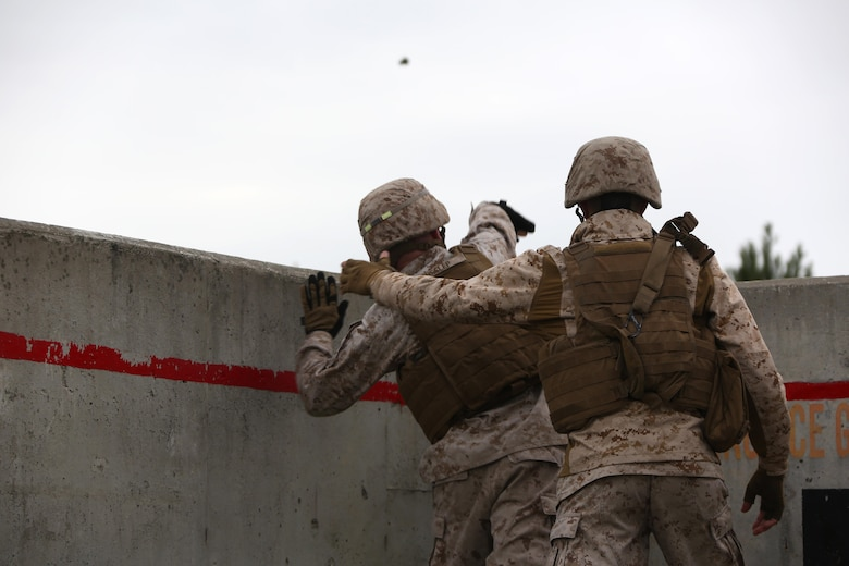 Cpl. Justin Heslep, left, throws An M69 Practice Grenade as Cpl. Nathan Queen supervises during a grenade and MK19 Grenade Launcher range at Marine Corps Base Camp Lejeune, N.C., Oct. 28, 2015. More than 70 Marines with 2nd Low Altitude Air Defense Battalion took turns handling the MK-19 and handheld grenades during the familiarization range. The range offered Marines the opportunity to build confidence and proficiency skills on some of the crew-served weapons they operate while providing security in a deployed environment. Heslep and Queen are both low altitude aerial defense gunners with the battalion. (U.S. Marine Corps photo by Cpl. N.W. Huertas/Released)