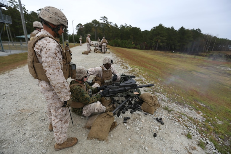 Marines fire rounds down range during a grenade and MK19 Grenade Launcher range at Marine Corps Base Camp Lejeune, N.C., Oct. 28, 2015. More than 70 Marines with 2nd Low Altitude Air Defense Battalion took turns handling the MK19 and handheld grenades during the familiarization range. The range offered Marines the opportunity to build confidence and proficiency skills on some of the crew-served weapons they operate while providing security in a deployed environment. (U.S. Marine Corps photo by Cpl. N.W. Huertas/Released)