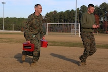The 2nd Marine Aircraft Wing Commanding General, Maj. Gen. Gary Thomas carries ammunition cans through the maneuver under fire course as he is timed by Cpl. Ethan Mussaw during a combat fitness test at Marine Corps Air Station Cherry Point, N.C., Dec. 4, 2015. The CFT is an annual requirement for all Marines to assess their physical capacity in a broad spectrum of combat-related tasks. 2nd MAW Marines maintain their combat readiness year-round in order to provide continuous support to the Marine Air-Ground Task Force. Thomas is the commanding general of 2nd MAW and Mussaw is an operations clerk with Marine Wing Headquarters Squadron 2. (U.S. Marine Corps photo by Cpl. N.W. Huertas/Released)