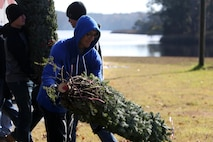 Private first class Sidney Livingston stacks trees for distribution during the 10th annual trees for troops event at Marine Corps Air Station Cherry Point, N.C., Dec. 8, 2015. More than 400 free trees were distributed to service members and their families as a symbol of brotherhood and appreciation from the community during the holiday season. Livingston is a bulk fuel specialist with Marine Wing Support Squadron 274. (U.S. Marine Corps photo by Cpl. N.W. Huertas/Released)