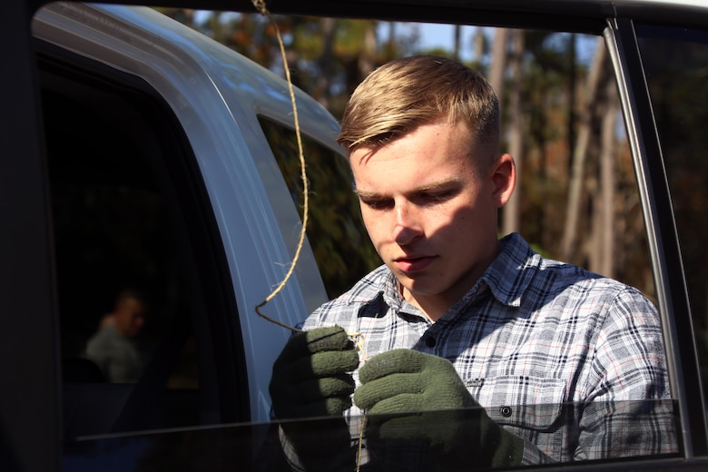 Lance Cpl. Jonah Merkle ties a tree to a vehicle during the 10th annual trees for troops event at Marine Corps Air Station Cherry Point, N.C., Dec. 8, 2015. More than 400 free trees were distributed to service members and their families as a symbol of brotherhood and appreciation from the community during the holiday season. Merkle is a bulk fuel specialist with Marine Wing Support Squadron 274. (U.S. Marine Corps photo by Cpl. N.W. Huertas/Released)