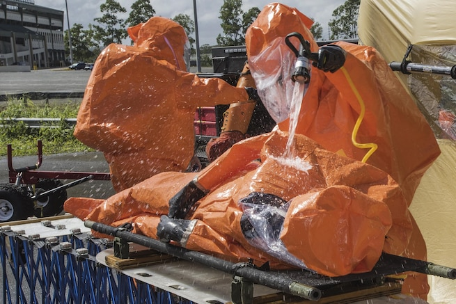 Army Staff Sgt. Rusty Greeno, right, rinses Air Force Tech. Sgt. August Hoaglund during decontamination for a man-down drill in Carolina, Puerto Rico, Jan. 26, 2016. Greeno and Hoaglund are assigned to the Vermont National Guard's 15th Civil Support Team. Vermont Army National Guard photo by Staff Sgt. Nathan Rivard