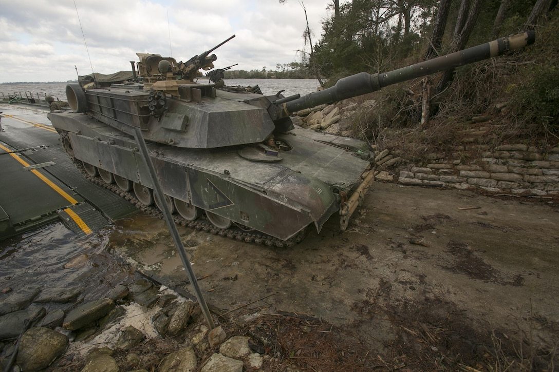Marines with Bridge Company, 8th Engineer Support Battalion, roll an M1A1 Abrams tank off of a seven-bay raft system after being transported across New River during a water-crossing operation at Camp Lejeune, N.C., Feb. 4, 2016. The unit boasts a wide range of raft systems and bridging that it is able to do to allow tactical vehicles to cross large bodies of water. (U.S. Marine Corps photo by Lance Cpl. Damarko Bones/Released)