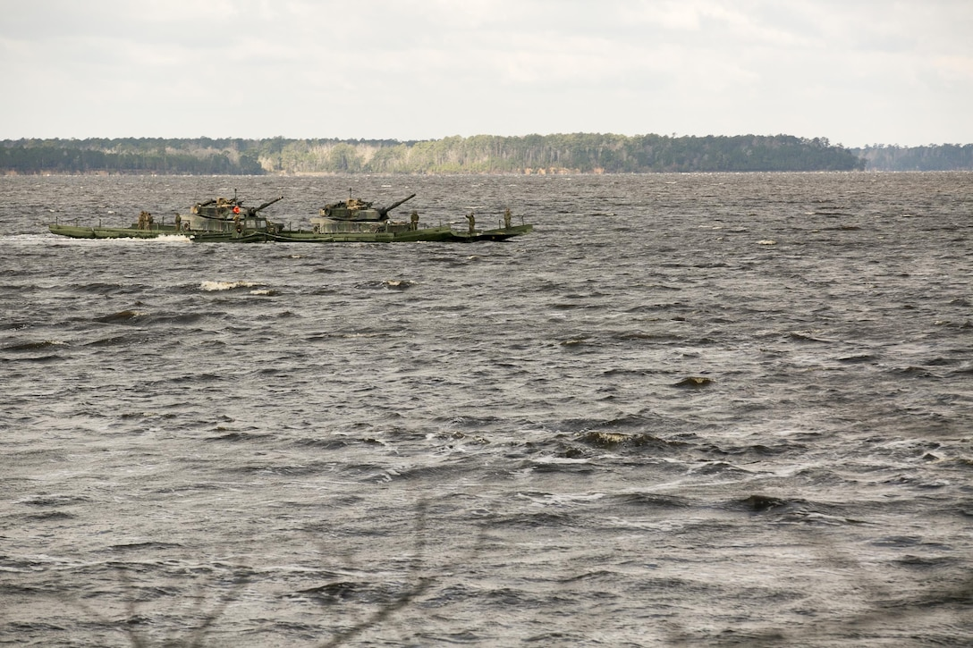 Marines with Bridge Company, 8th Engineer Support Battalion, transport two M1A1 Abrams tanks across New River, using a seven-bay raft system during a water-crossing operation at Camp Lejeune, N.C., Feb. 4, 2016. The raft increases mobility of tactical vehicles by allowing the vehicles to cross any body of water regardless of size. (U.S. Marine Corps photo by Lance Cpl. Damarko Bones/Released)
