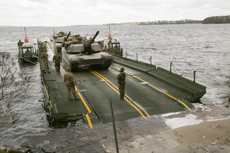 Marines with Bridge Company, 8th Engineer Support Battalion, prepare to unload two M1A1 Abrams tanks following their transport across New River by using a seven-bay raft system during a water-crossing operation at Camp Lejeune, N.C., Feb. 4, 2016. The unit boasts a wide range of raft systems and bridging equipment, which enables tactical vehicles to cross large bodies of water. (U.S. Marine Corps photo by Lance Cpl. Damarko Bones/Released)