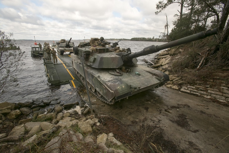 Marines with Bridge Company, 8th Engineer Support Battalion, roll an M1A1 Abrams tank off of a seven-bay raft system after being transported across New River during a water-crossing operation at Camp Lejeune, N.C., Feb. 4, 2016. The company specializes in allowing units to travel over bodies of water, which in turn increases the mobility of the unit being transported. (U.S. Marine Corps photo by Lance Cpl. Damarko Bones/Released)