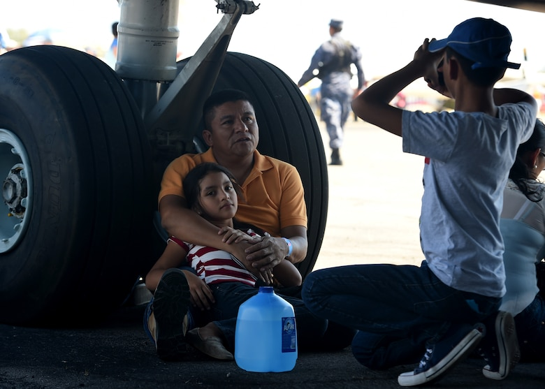Citizens from El Salvador sit under a U.S. Air Force C-17 Globemaster III cargo aircraft, 58th Airlift Squadron, at Ilopango International Airport in San Salvador, El Savador, Jan. 30, during the 2016 Ilopango Airshow. The C-17 was sent from Altus Air Force Base, Okla., to foster relationships between the U.S. and El Salvador. The aircraft was setup as a static display for the attendees to view and learn about some of its capabilities. (U.S. Air Force photo by Senior Airman Franklin R. Ramos/Released)