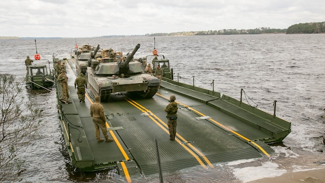 Marines with Bridge Company, 8th Engineer Support Battalion, prepare to unload two M1A1 Abrams tanks following their transport across New River by using a seven-bay raft system during a water-crossing operation at Marine Corps Base Camp Lejeune, N.C., Feb. 4, 2016. The unit boasts a wide range of raft systems and bridging equipment, which enables tactical vehicles to cross large bodies of water.