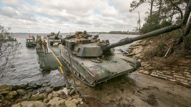 Marines with Bridge Company, 8th Engineer Support Battalion, roll an M1A1 Abrams tank off of a seven-bay raft system after being transported across New River during a water-crossing operation at Marine Corps Base Camp Lejeune, N.C., Feb. 4, 2016. The company specializes in allowing units to travel over bodies of water, which in turn increases the mobility of the unit being transported.