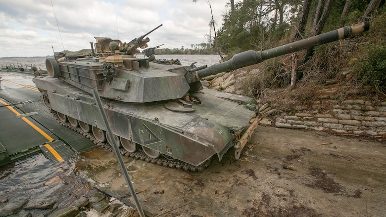 Marines with Bridge Company, 8th Engineer Support Battalion, roll an M1A1 Abrams tank off of a seven-bay raft system after being transported across New River during a water-crossing operation at Marine Corps Base Camp Lejeune, N.C., Feb. 4, 2016. The unit boasts a wide range of raft systems and bridging that it is able to do to allow tactical vehicles to cross large bodies of water.