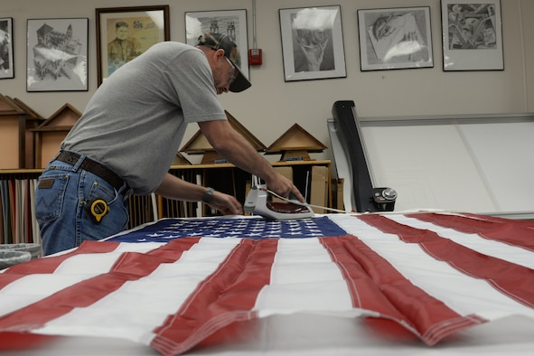 Chris Holland, Arts and Crafts Center assistant framer, irons a U.S. flag to be placed in a shadow box Feb. 2, 2016, Keesler Air Force Base, Miss. The wood shop builds shadow boxes, coin holders and custom frames to order. (U.S. Air Force photo by Airman 1st Class Travis Beihl)