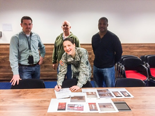 DLA Distribution Europe commander Army Lt. Col. Krista Hoffman signs the last official receipt for the Intermediate Staging Base in Incirlik, Turkey, alongside Matt Merrill, chief of Operations Division, far left, Richard Holland, accountable officer, back center, and Derrick White, chief of Inventory Division, far right.