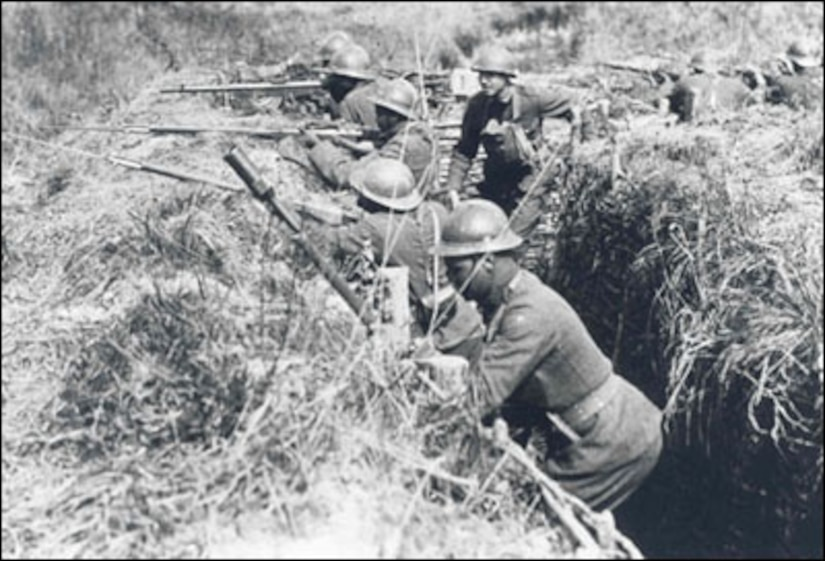 African-American Soldiers (and one of their white officers) of the 369th Infantry practice what they will soon experience, fighting in the trenches of the Western Front. They are wearing French helmets and using French issued rifles and equipment, the logic being that since they were fighting under French command, it was easier to resupply them from the French system than trying to get American-issued items.