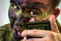 "Army 1st Lt. Oliver Salman puts on camouflage paint before a night static-line jump during ""large package week"" training operations on Pope Army Airfield, N.C., Feb. 6, 2016. The training helps prepare airmen and soldiers for a subsequent joint access exercise. Air Force photo by Staff Sgt. Marianique Santos"