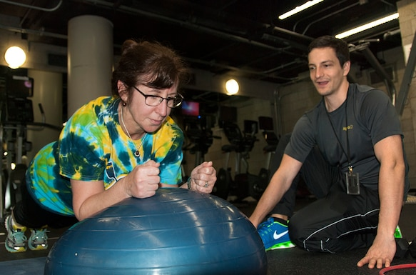 An employee works on core strength in a one-on-one workout with an HQC Fitness Center coach