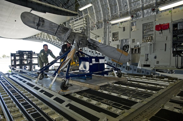 Tech. Sgt. Michael Smith, a loadmaster assigned to the 300th Airlift Squadron, Joint Base Charleston, South Carolina, pushes an aircraft propellar into the cargo area of a C-17 Globemaster III aircraft. Reservists assigned to the 300 AS assisted the U.S. Coast Guard with transporting several MH-65 Dolphin helicopters and various supplies Feb. 5-7, 2016. (U.S. Air Force photo by SSgt. Bobby Pilch)