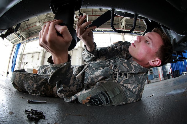 A soldier prepares an AH-64 Apache helicopter for transport on Fort Bragg, N.C., Feb. 2, 2016. Army photo by Staff Sgt. Christopher Freeman
