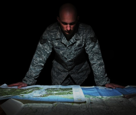 Staff Sgt. Darrell Prior, a Terminal Instrument Procedures (TERPS) specialist with Air Mobility Command, examines a map of Colombia at MacDill Air Force Base, Fla., Feb. 2, 2016. As a whole, the MacDill TERPS office ensures all Defense Department aircraft safely land in Central America, South America, the Caribbean, and Mexico by evaluating the host nation's procedures and applying Air Force criteria. (U.S. Air Force photo illustration/Senior Airman Danielle Quilla)