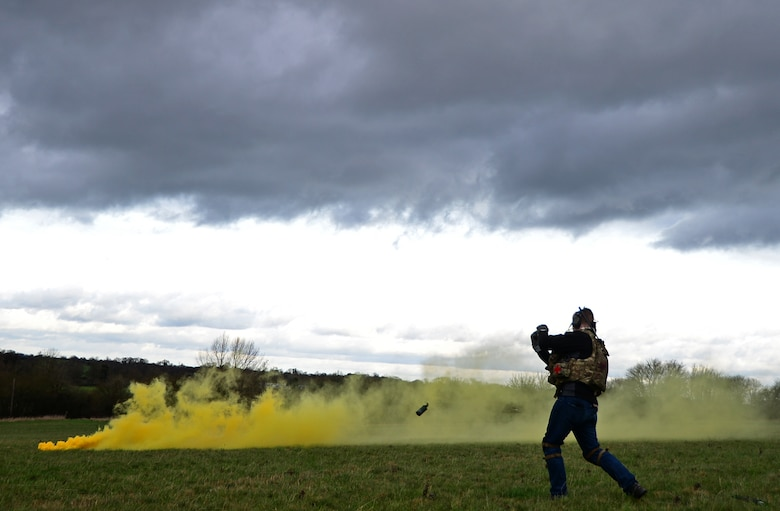 Staff Sgt. Joseph Bland, 56th Rescue Squadron special missions aviator, throws a smoke grenade during a combat search and rescue task force training exercise near Hinderclay, England, Feb. 4, 2016. Airmen assigned to the 56th and 57th RQSs performed various CSAR maneuvers to respond to a simulated threat scenario. (U.S. Air Force photo/Senior Airman Erin Trower)